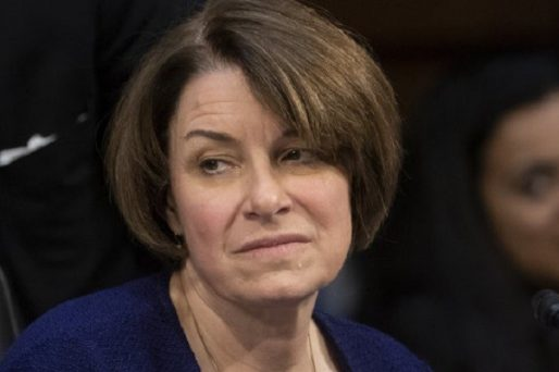 minnesota senator amy klobuchar frowning while sitting at a panel