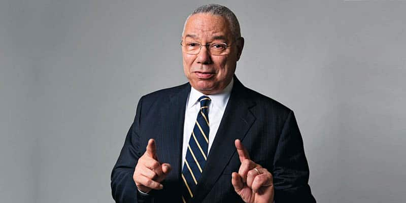 Colin Powell pointing his index fingers upwards