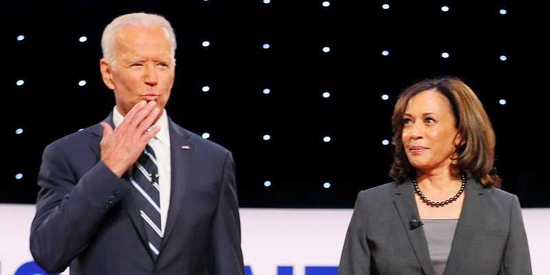 Joe Biden blowing a kiss to the audience with Kamala Harris standing to the right