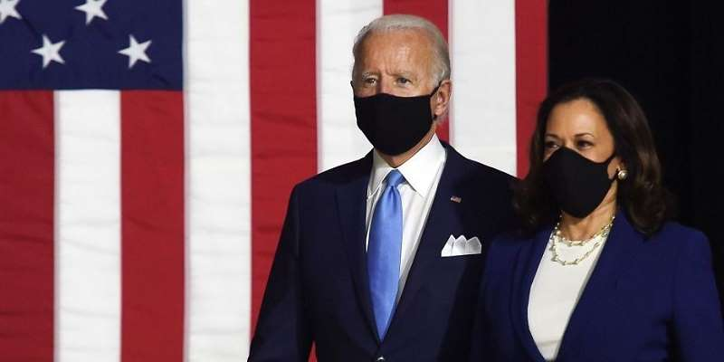 Biden standing next to Harris with face masks on in front of a US flag