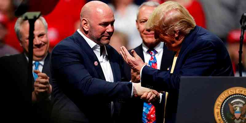 Dana White shaking hands with Donald Trump as he approaches a podium
