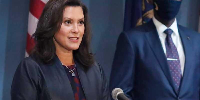 MI Governor Gretchen Whitmer speaking at a podium with a masked person standing to her right