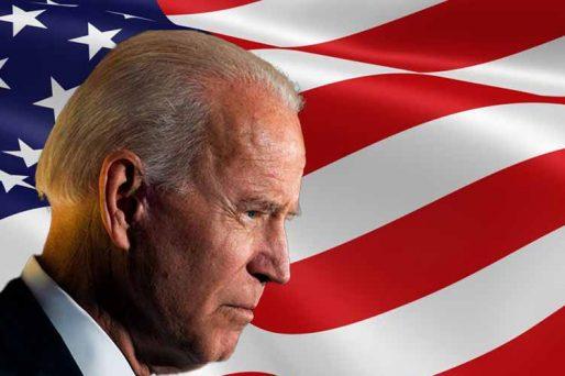 Joe Biden in profile in front of an American flag