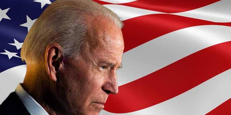 Joe Biden in profile in front of an American flag